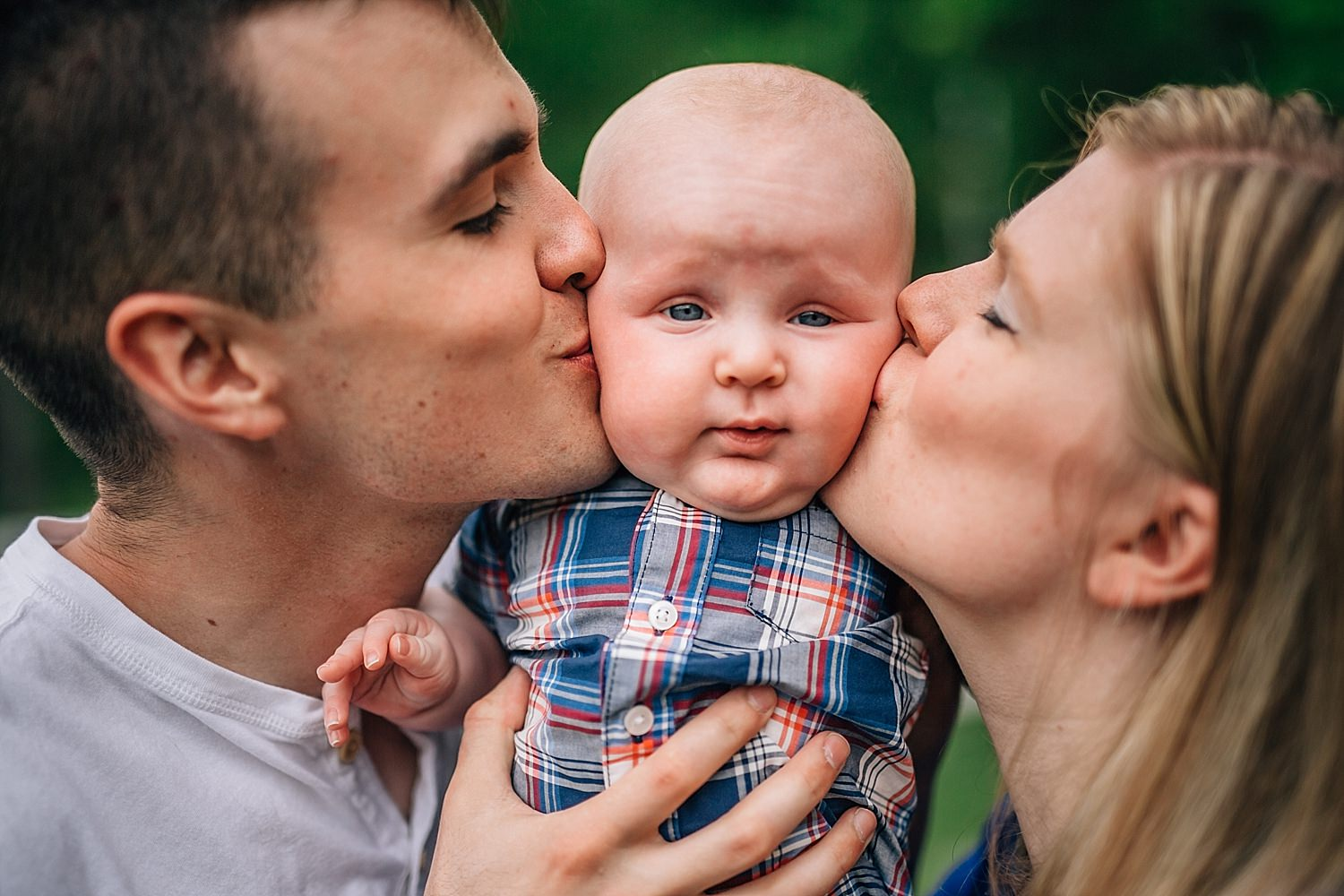 parents kissing baby cheeks in family pictures
