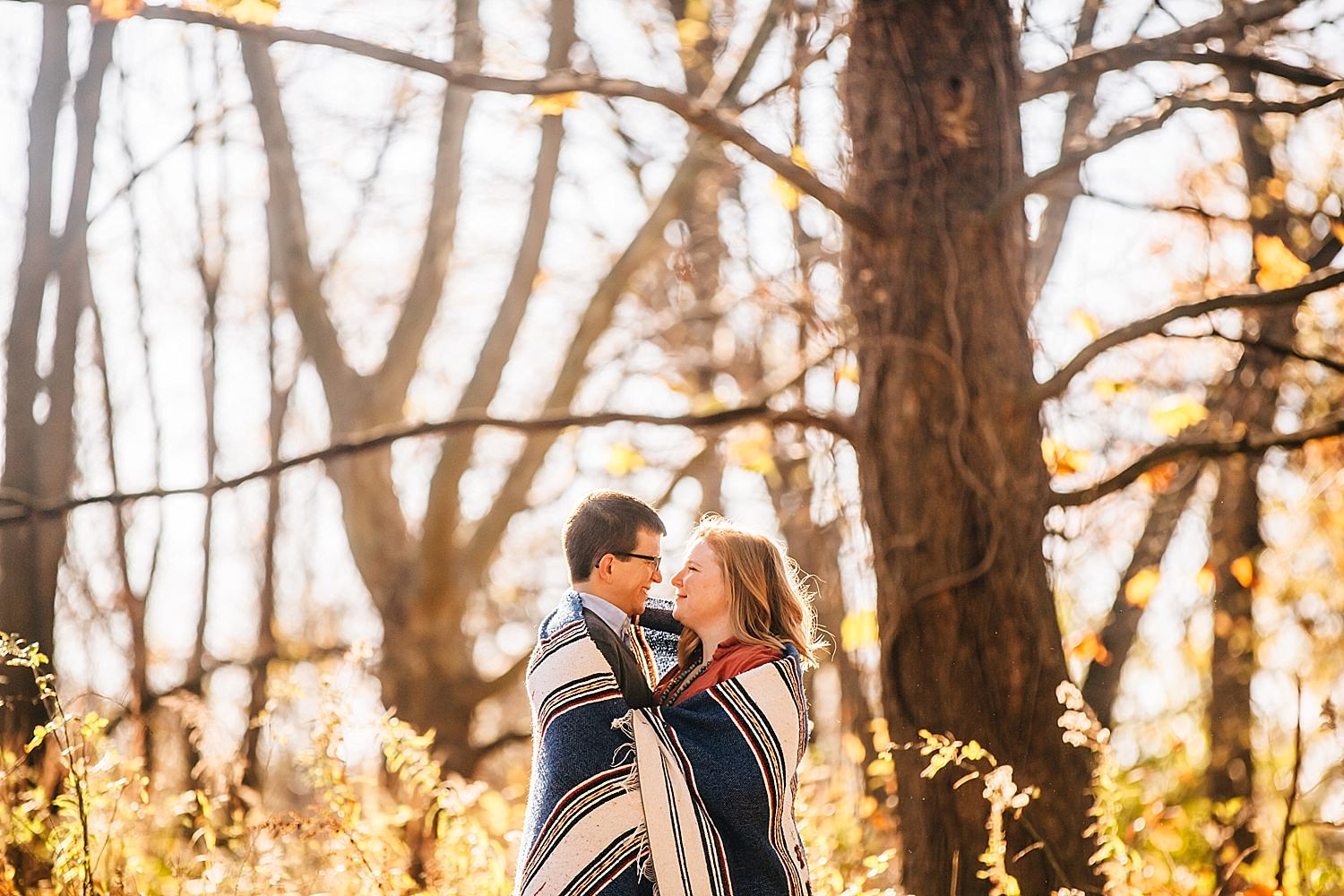 engaged couple cuddles in blanket in westerville ohio