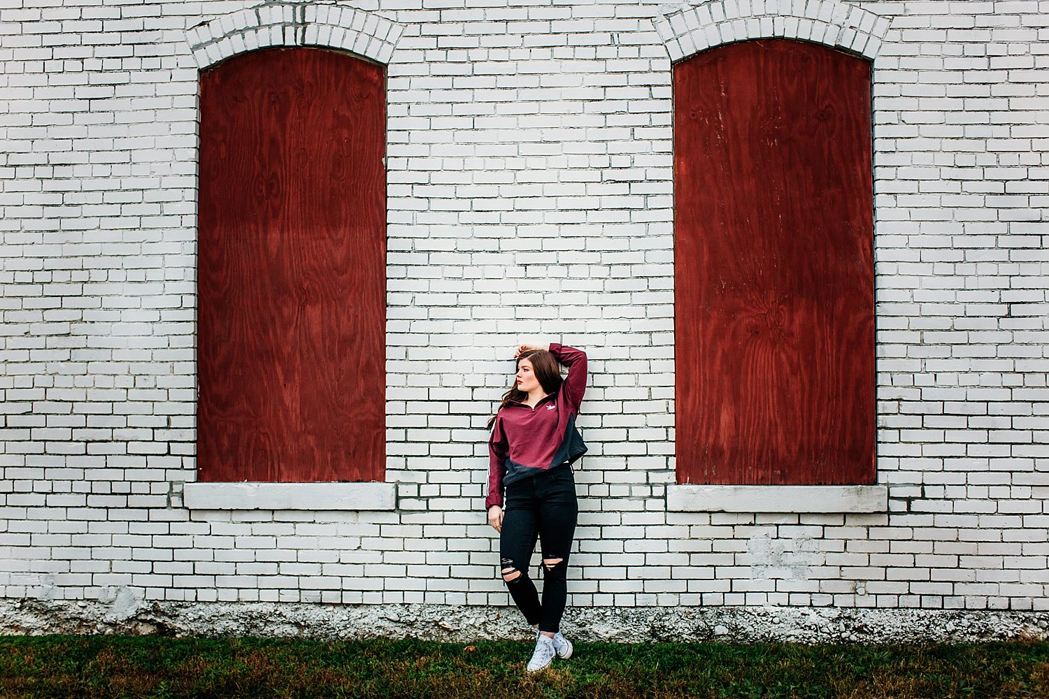 senior portrait of girl leaning against brick wall in newark ohio by sara devere
