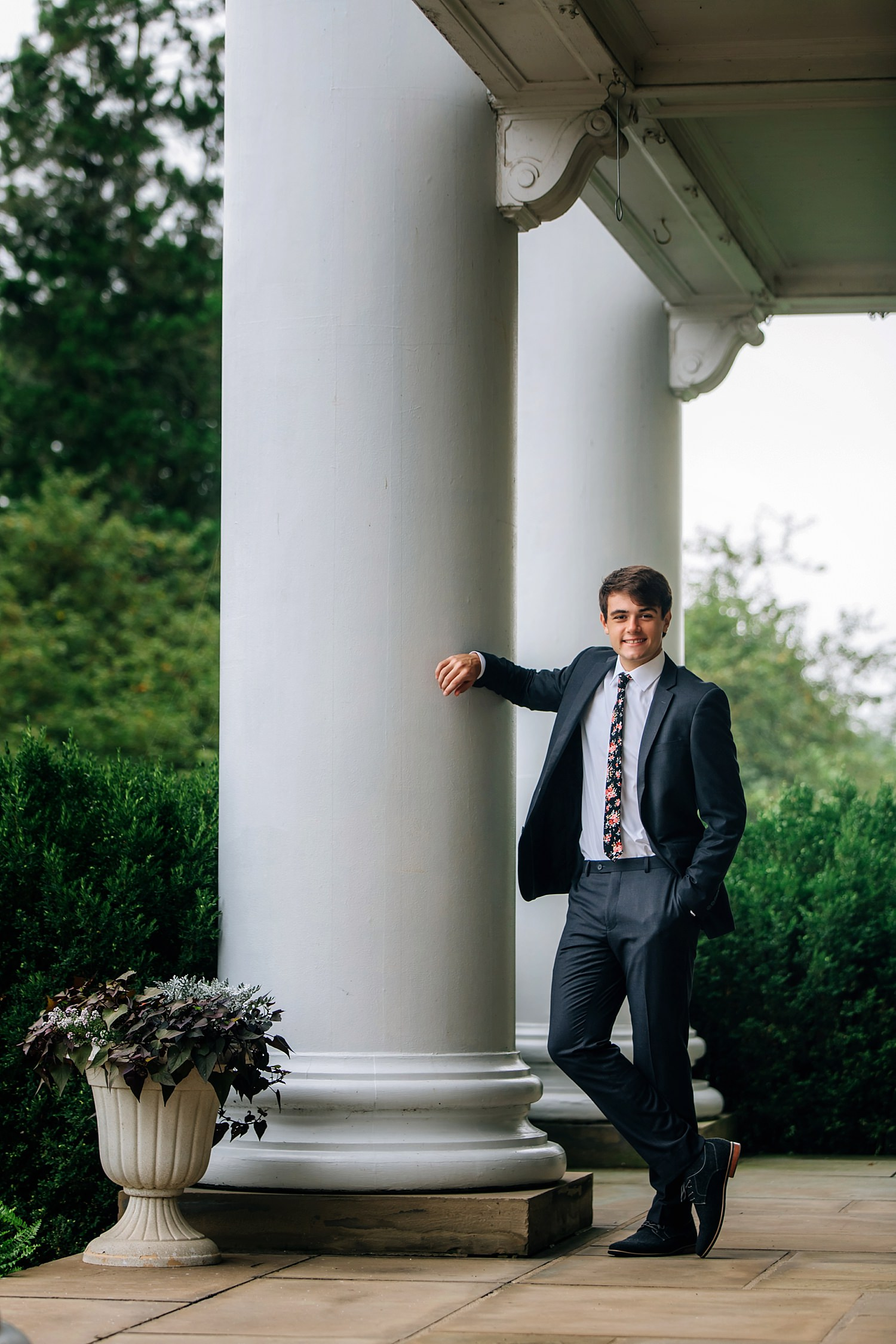 guys senior portraits posing in suit outdoors leaning against pillar at bryn du mansion