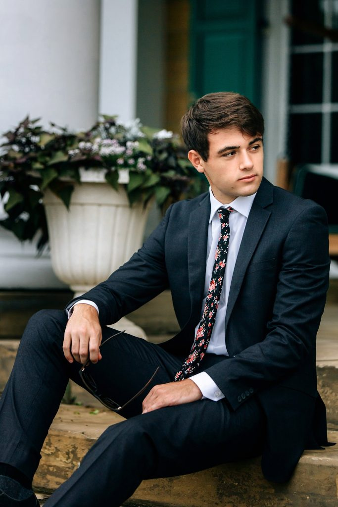 guys senior portraits posing in suit outdoors sitting at bryn du mansion