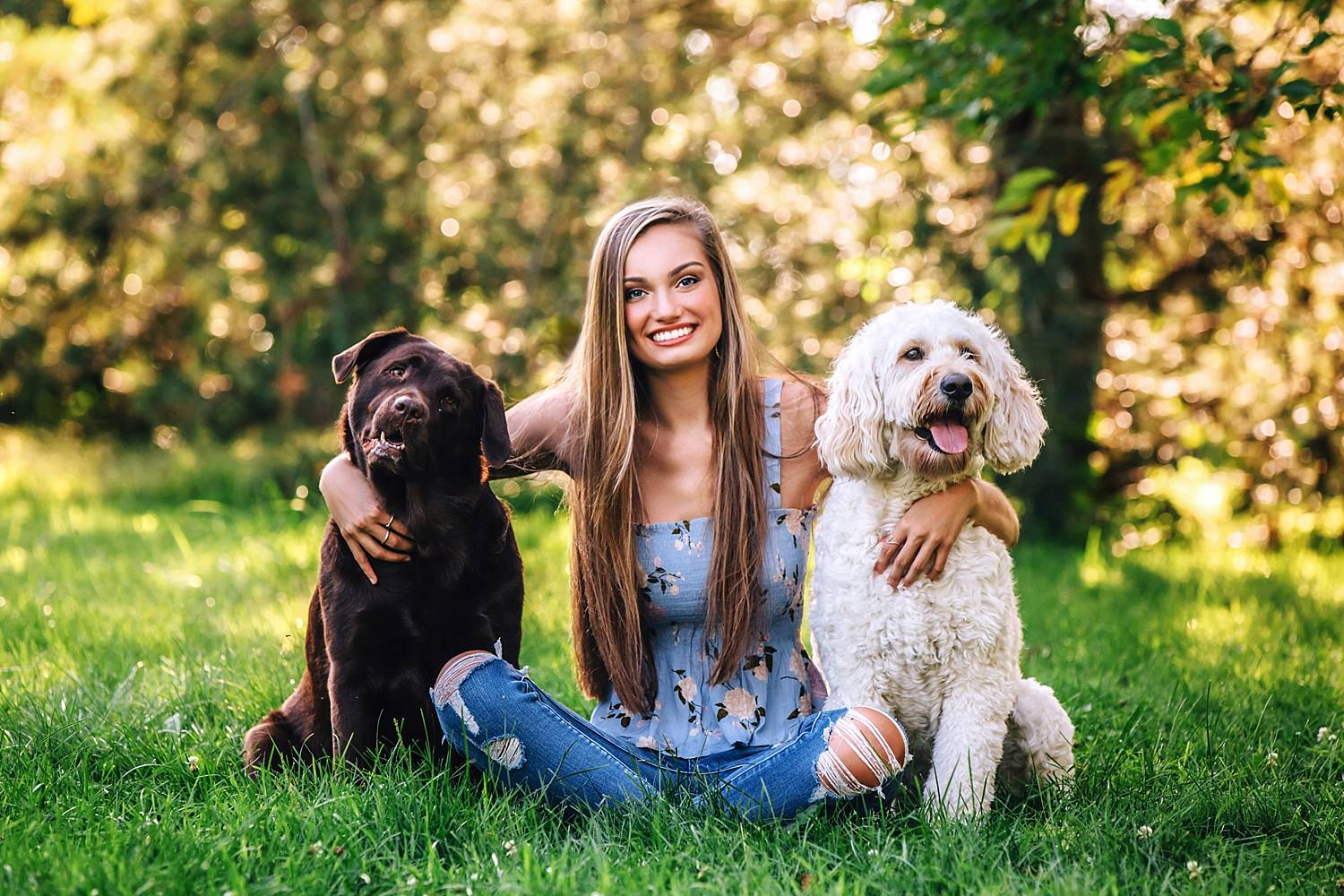 girl posing with dogs for senior portraits in field outside
