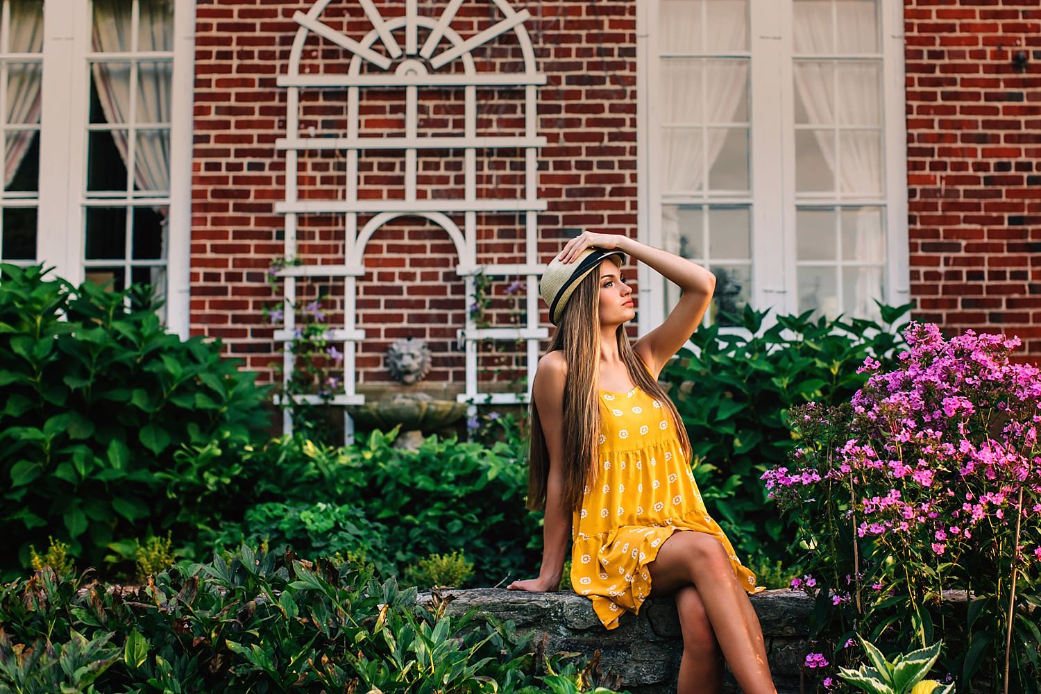 girl posing with hat in garden in sun for senior portraits