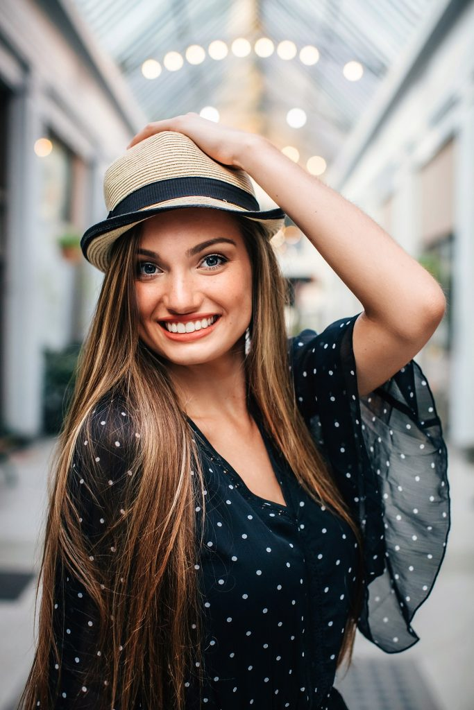 girl smiling with cute hat indoors posing for senior portraits