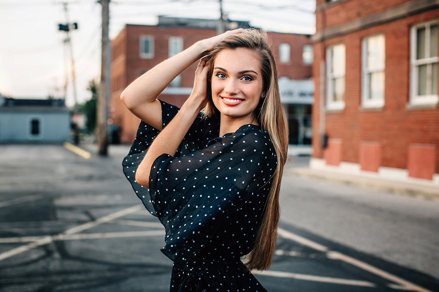girl smiling with hands in hair wearing polka dot dress posing in front of patterned wall for senior portraits by sara devere formerly sara long photography
