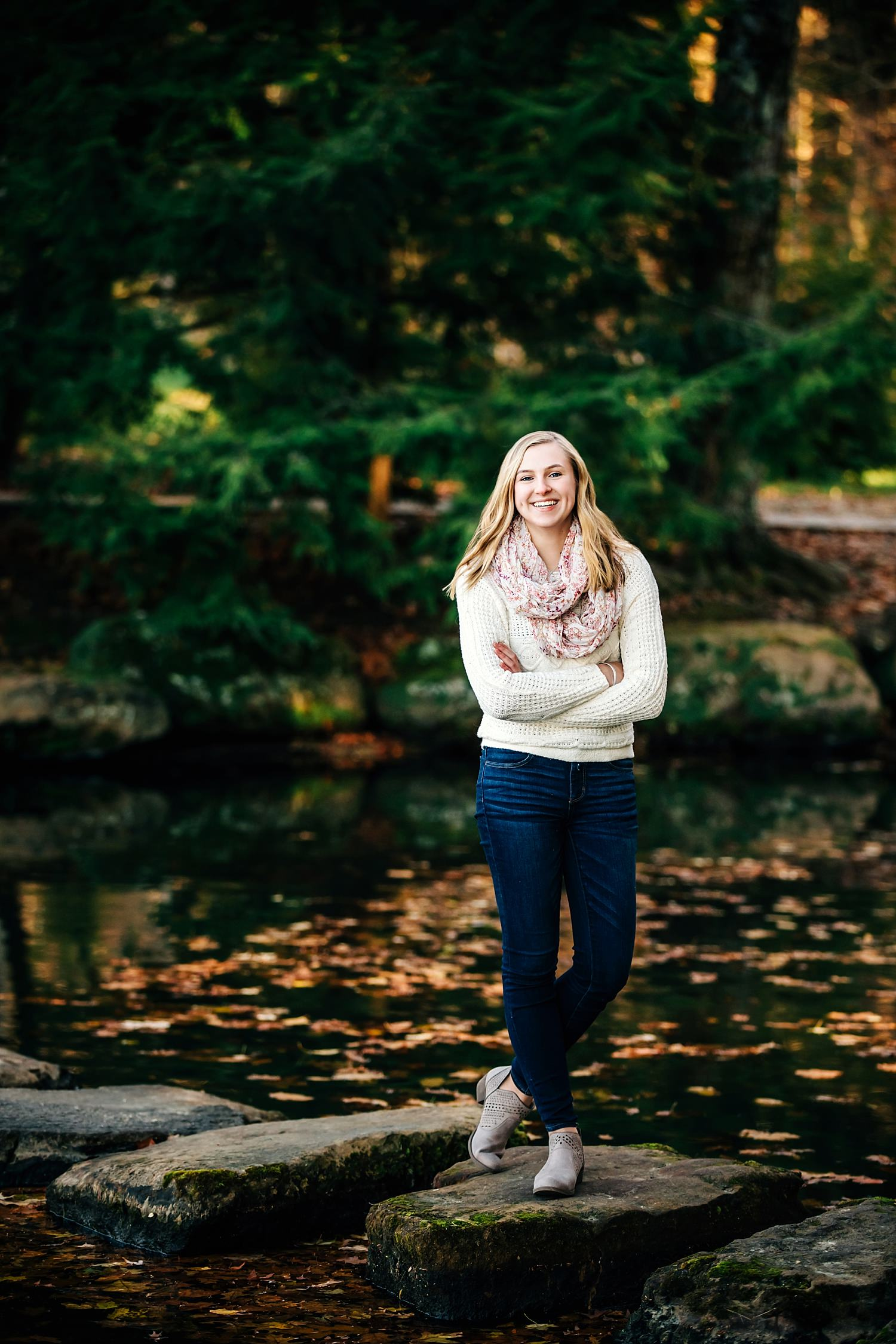 girl posing for senior portraits near water wearing sweater and scarf in granville ohio by sara devere
