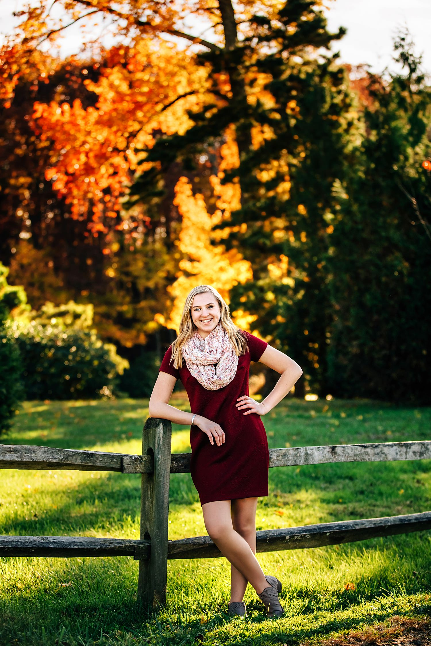 girl posing for senior portraits leaning against fence with fall colors behind her in granville ohio