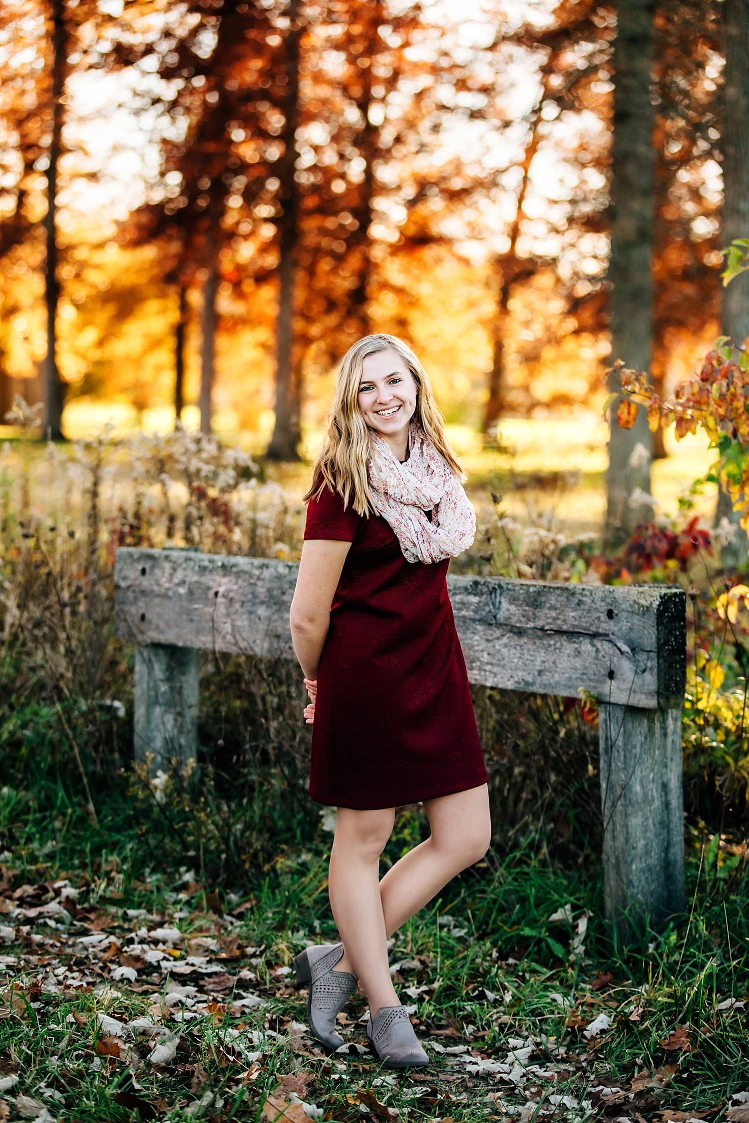 girl standing on bridge in woods with fall colors behind her for senior portraits in granville ohio