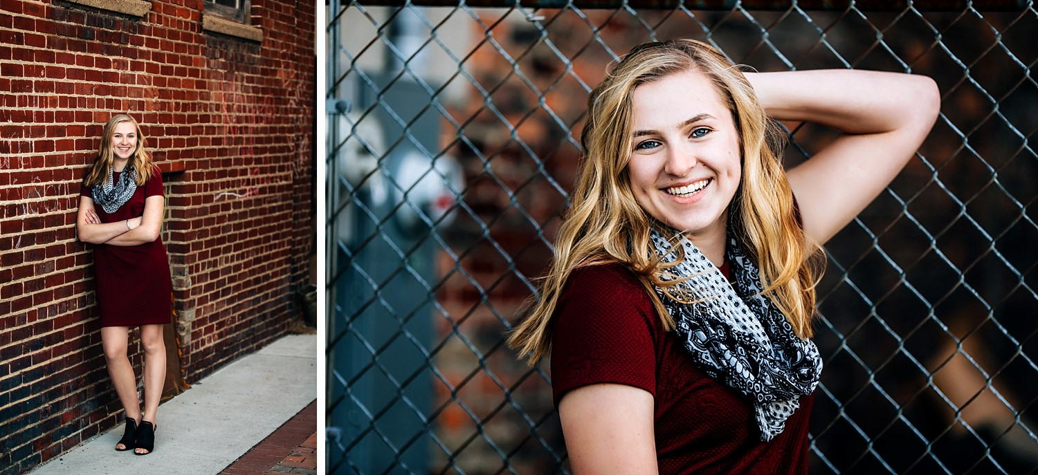 girl posing in urban city against brick wall smiling for senior portraits in newark ohio