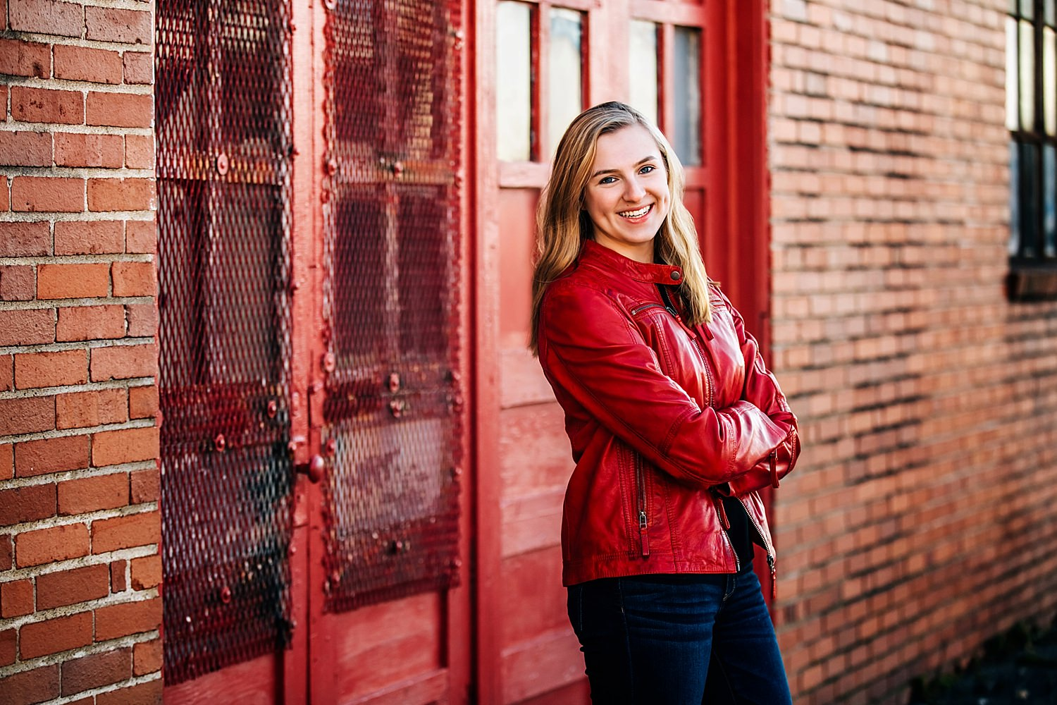 girl posing against red doors wearing red jacket smiling during senior portraits in newark ohio