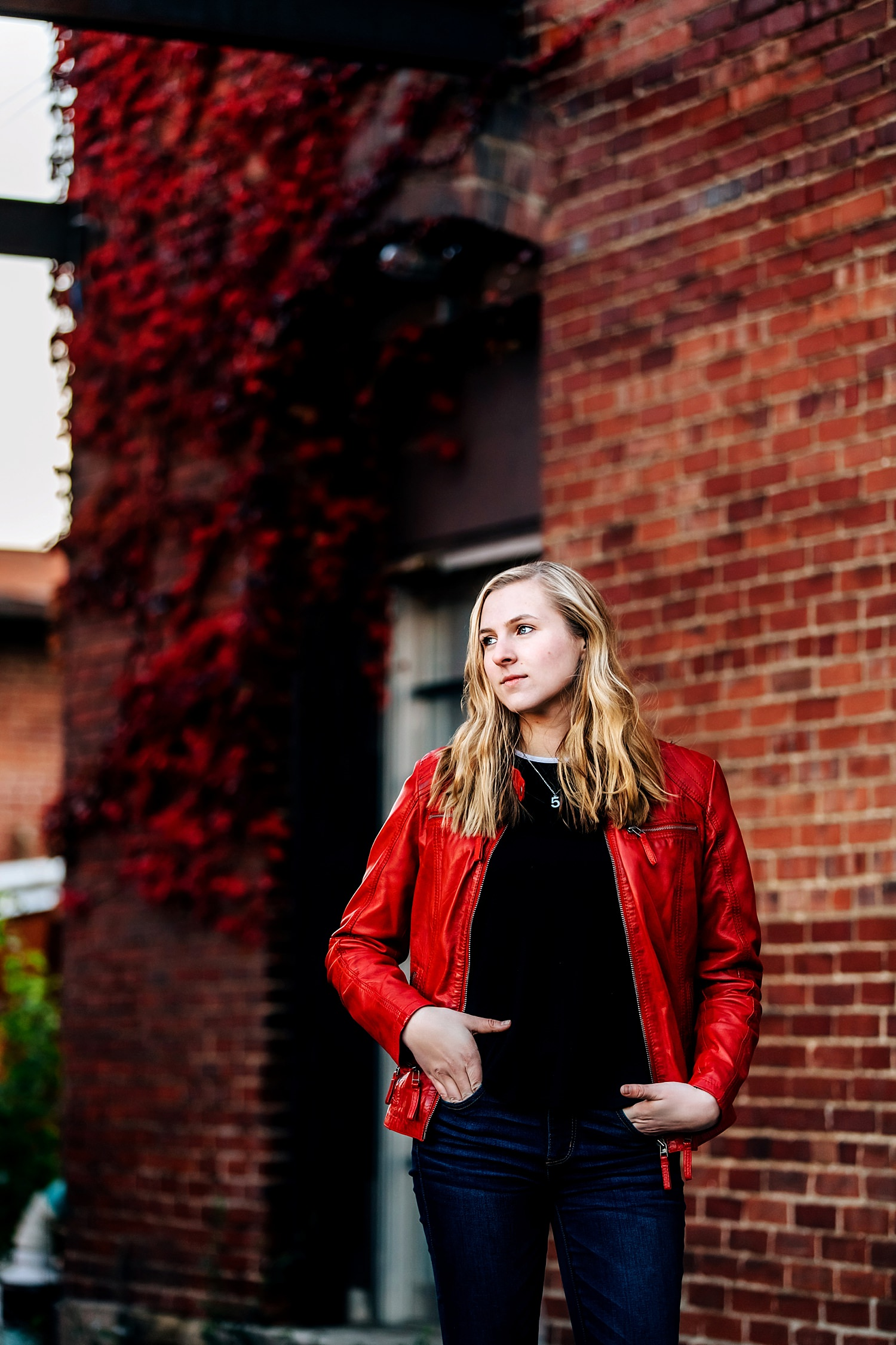 senior portrait against brick wall with red ivy in background in newark ohio