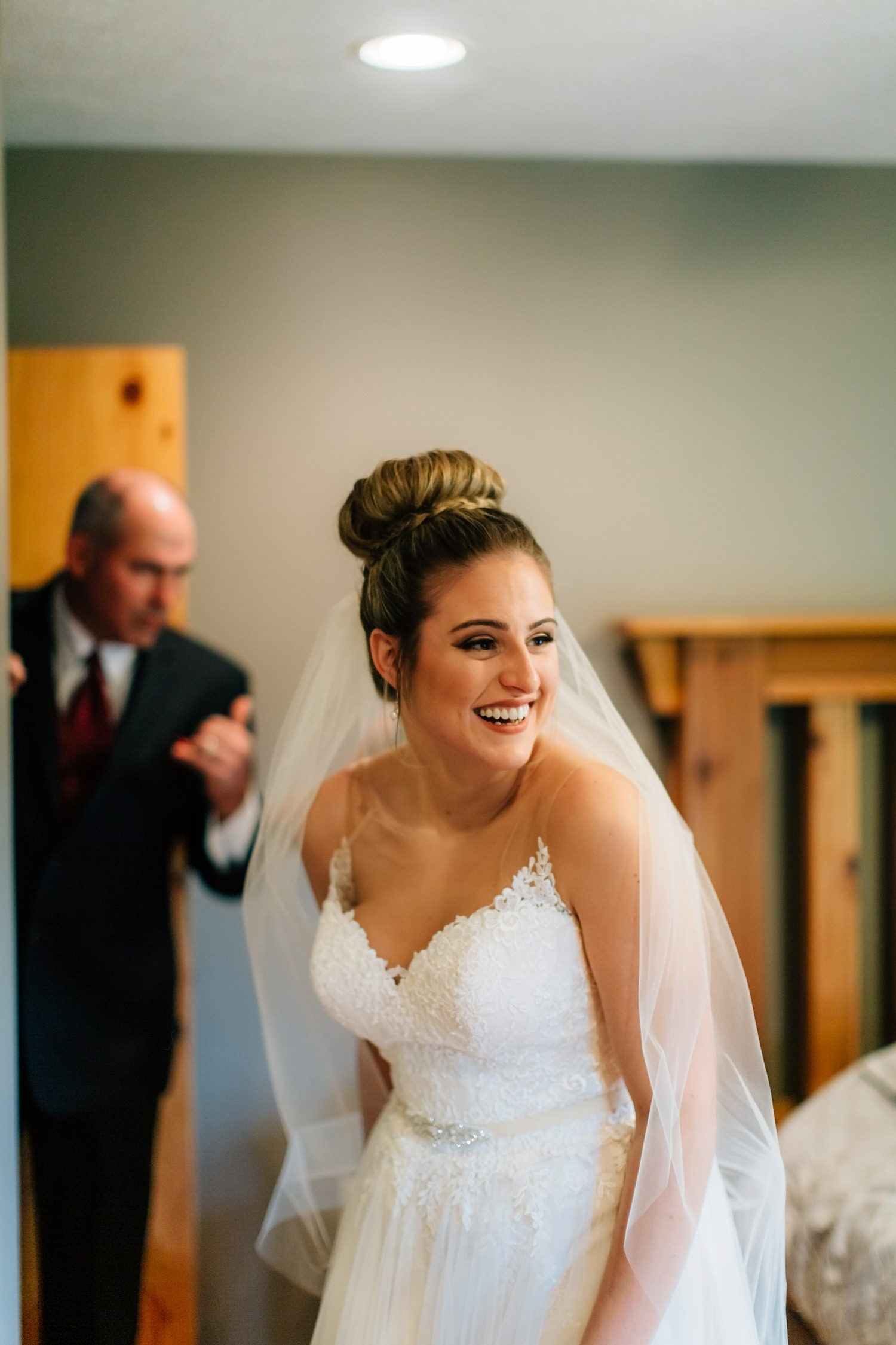 bride smiling while getting ready in wedding dress before backyard ceremony