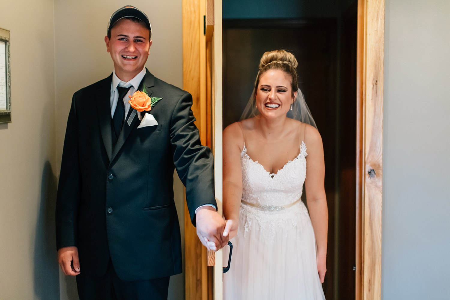 bride and groom hold hands around corner for a special moment before backyard ceremony in johnstown ohio