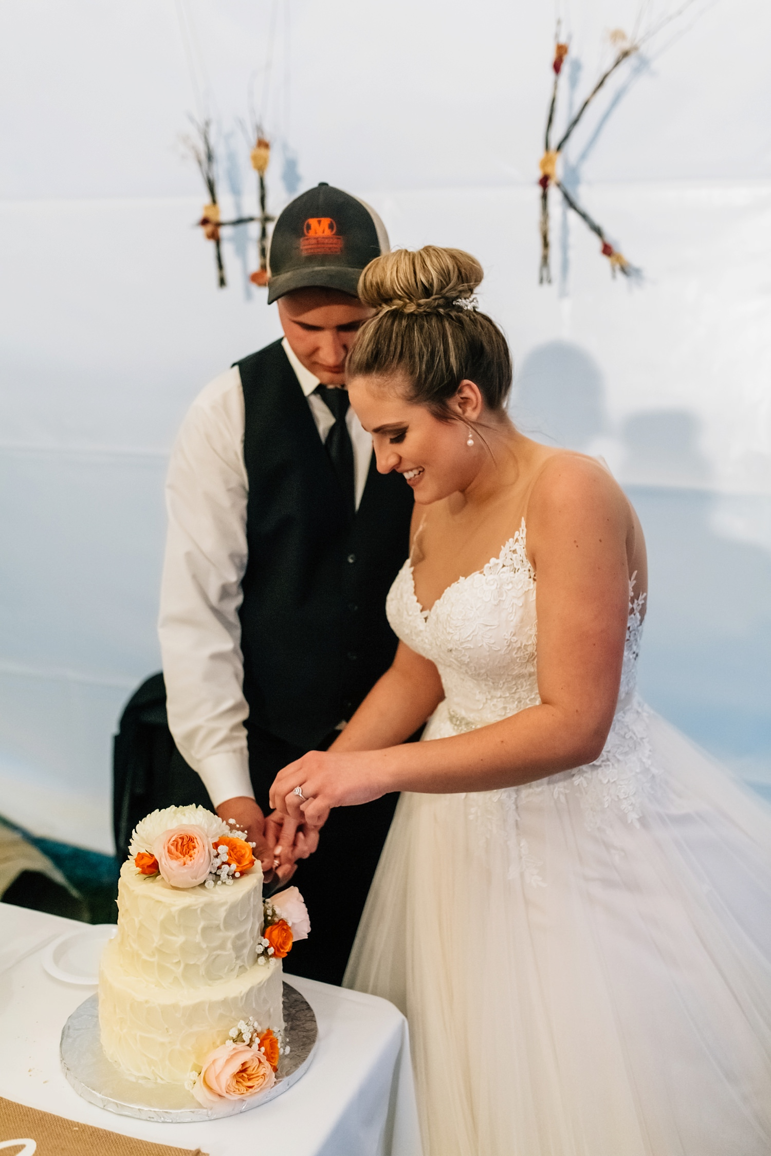 bride and groom cut the cake during tent reception at intimate backyard wedding ceremony in johnstown ohio