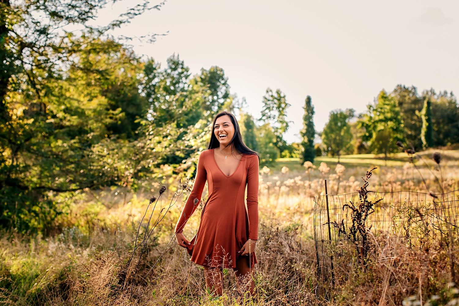 girl laughing in field playing with her dress for senior portraits during summer in newark ohio