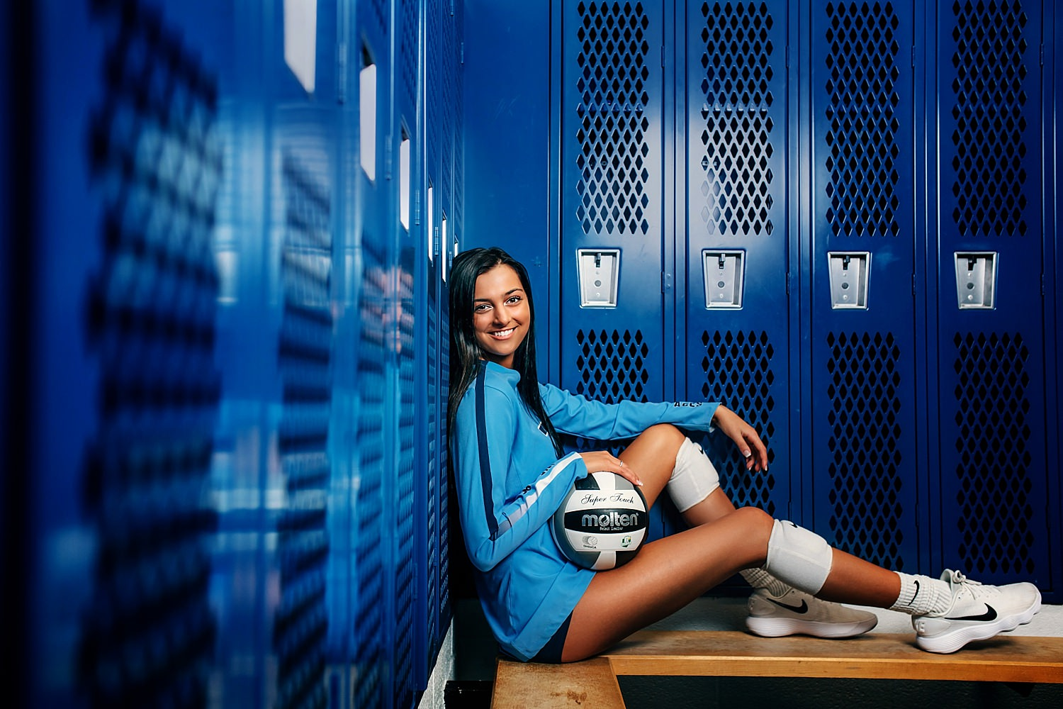 volleyball senior portrait poses with ball in locker room in granville high school