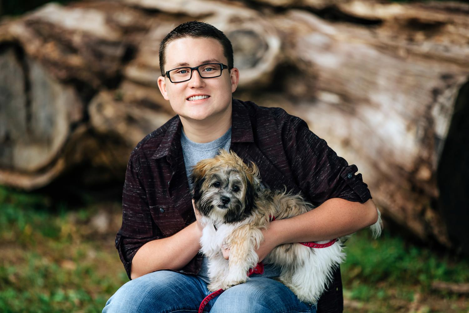 guy posing outdoors with puppy for senior portraits at deer haven park in delaware ohio