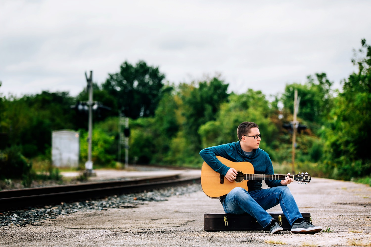 guy posing with guitar near train tracks in delaware ohio
