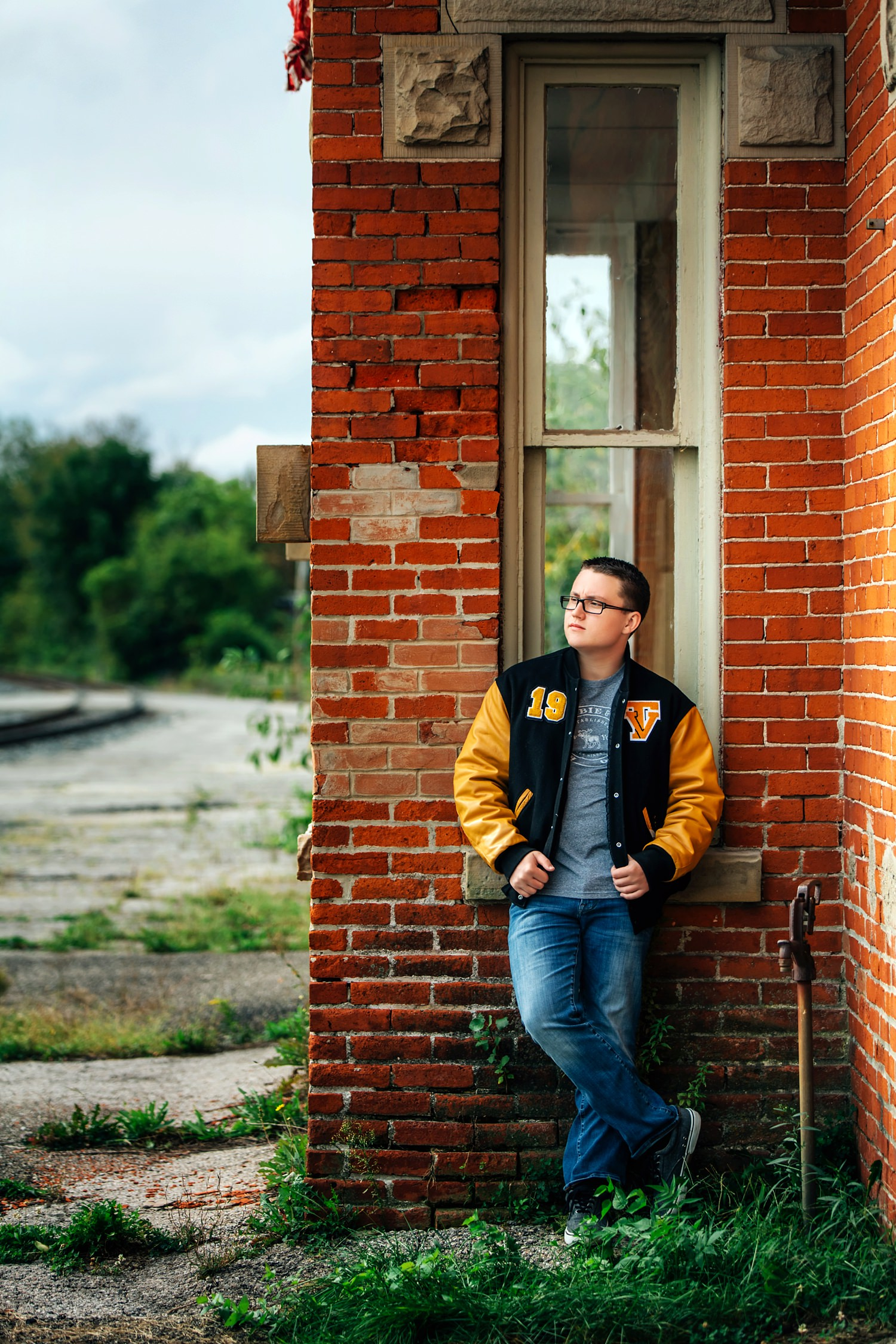 guy posing naturally against brick wall wearing letter jacket for senior portraits in delaware ohio