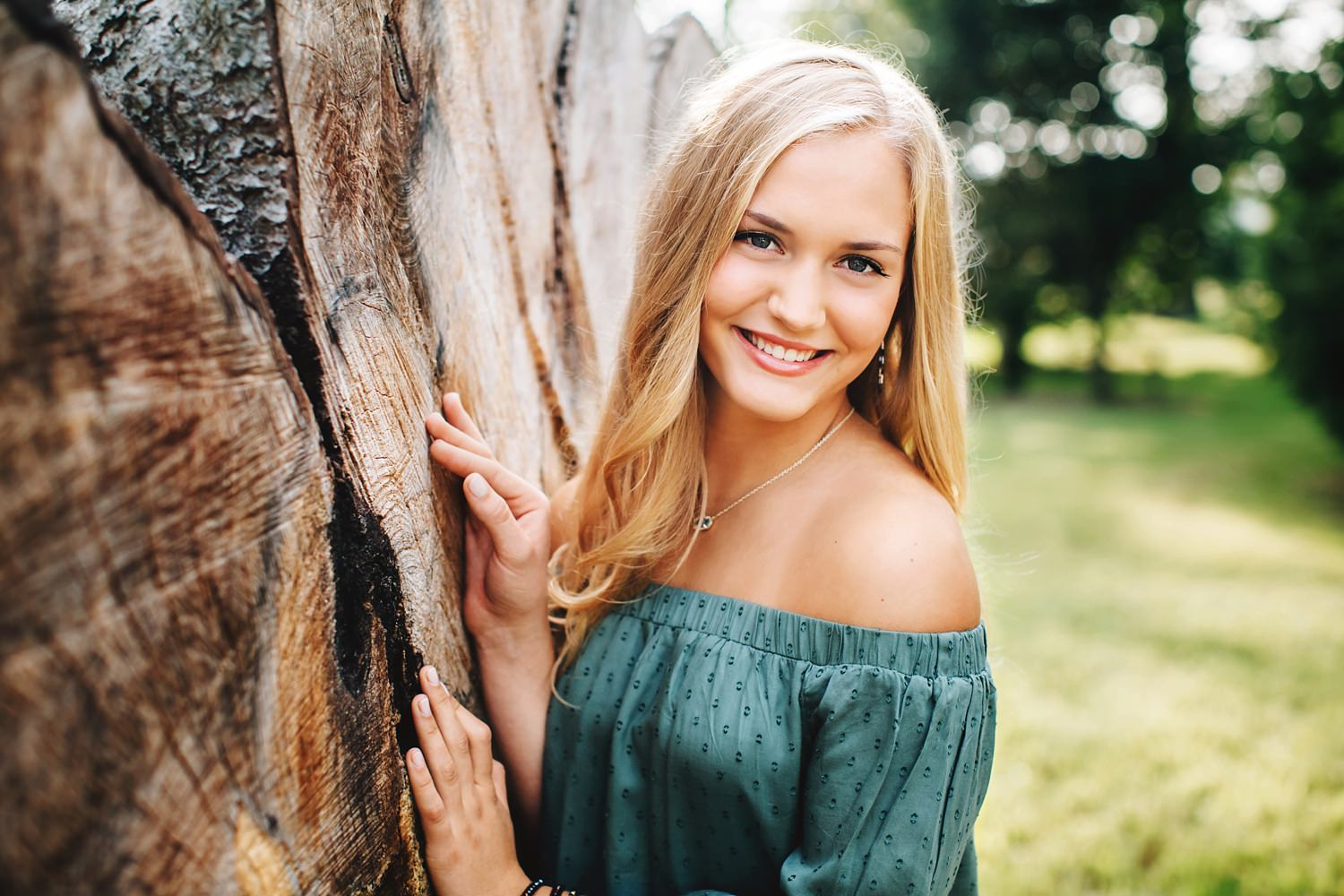 girl posing against tree smiling with long hair for senior portraits in granville ohio by sara devere formerly sara long photography