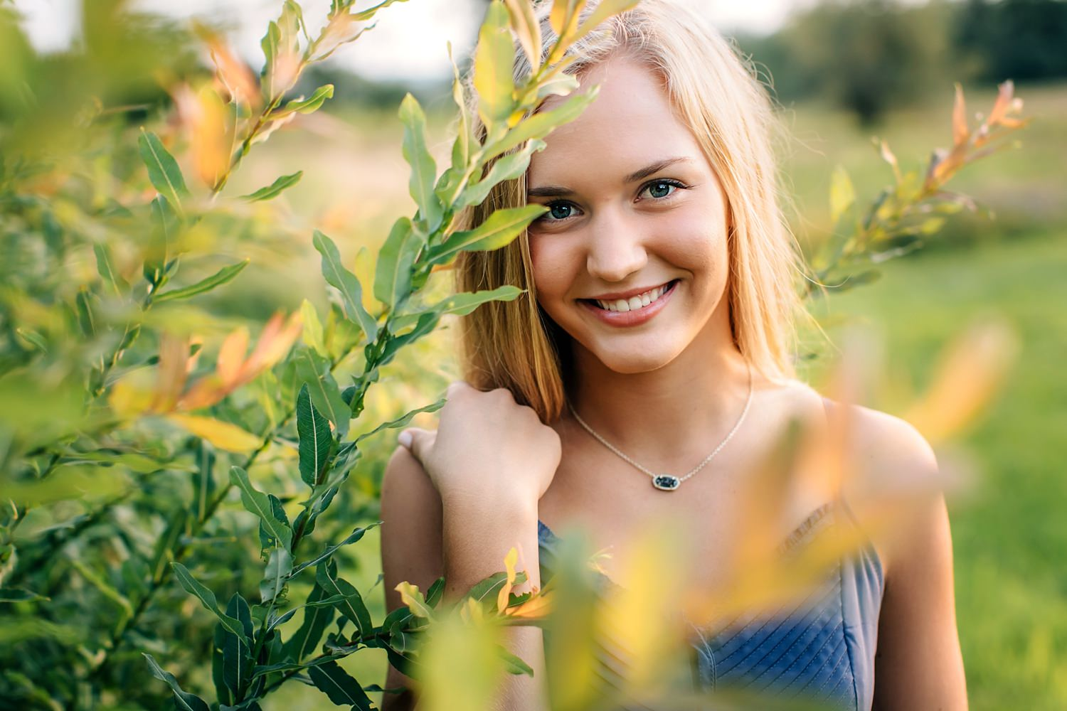 girl smiling in garden posing for natural senior portraits outside