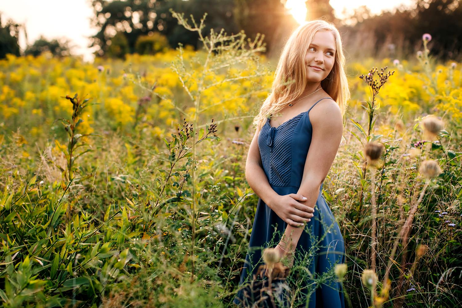 girl standing in goldenrod field during golden hour for natural senior portraits by sara devere formerly sara long photography