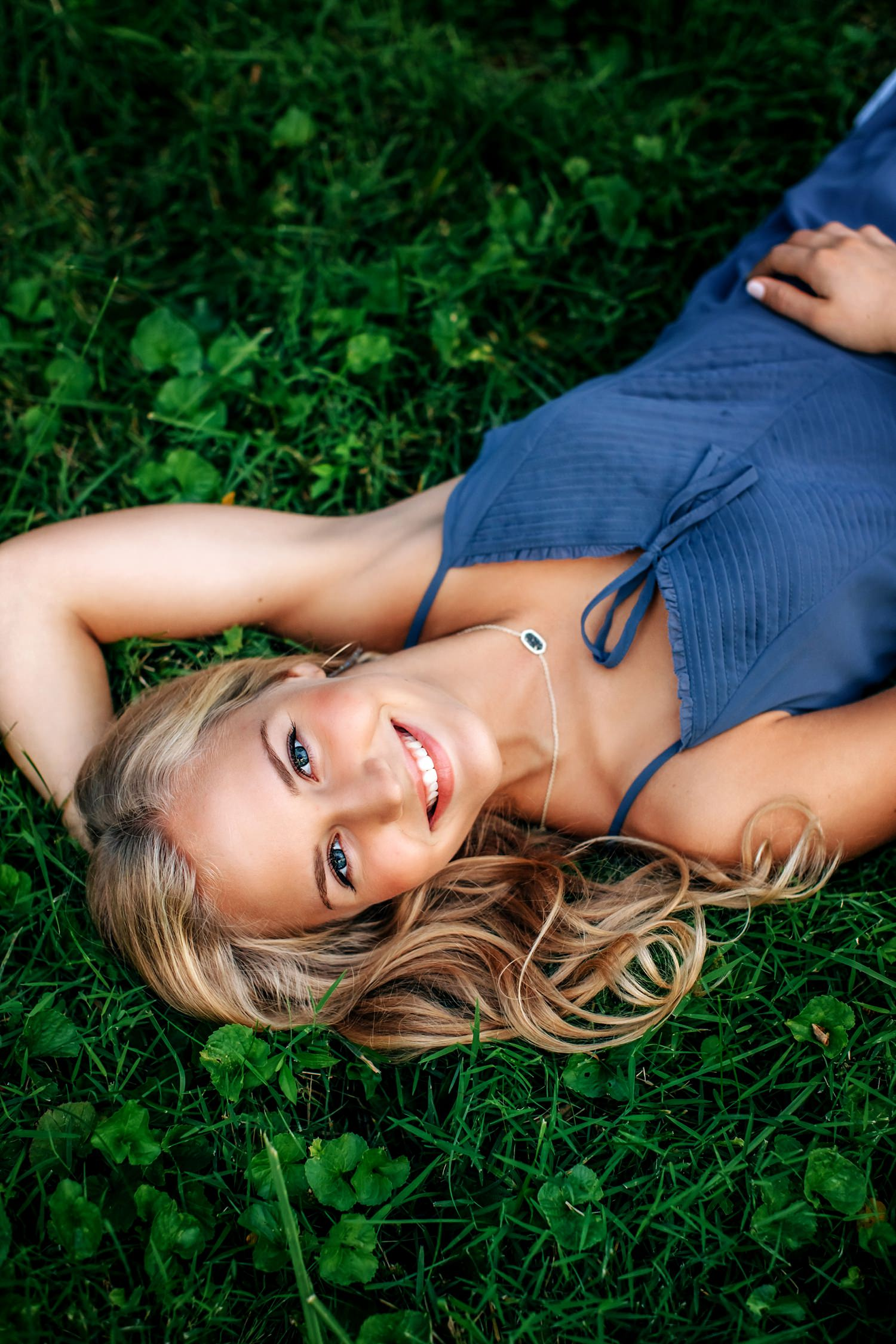 girl laying on back with hand behind head in grass smiling posing for senior portraits