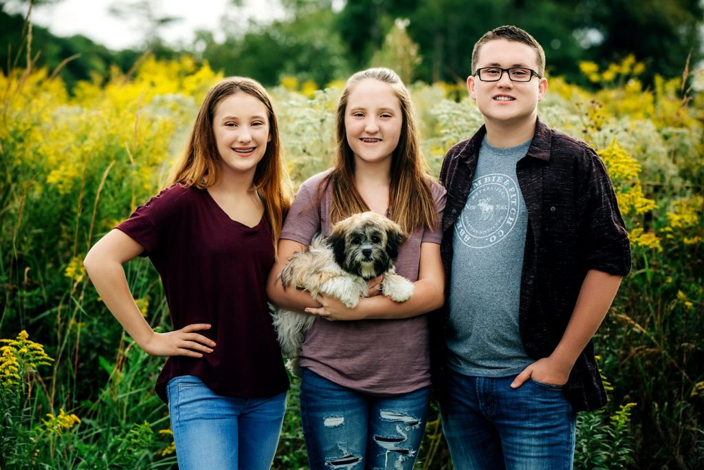 two sisters one brother and dog pose in wildflower field for family portraits at deer haven park in delaware ohio