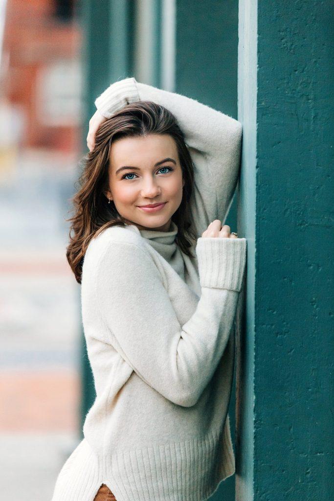 senior portrait in urban city leaning against wall in newark ohio