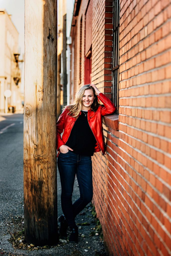 girl posing in city against brick wall for senior portraits in newark ohio