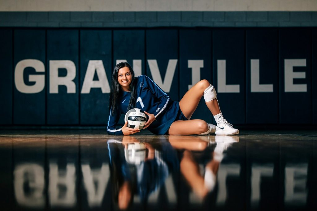 volleyball senior portrait poses with ball in gym in granville high school